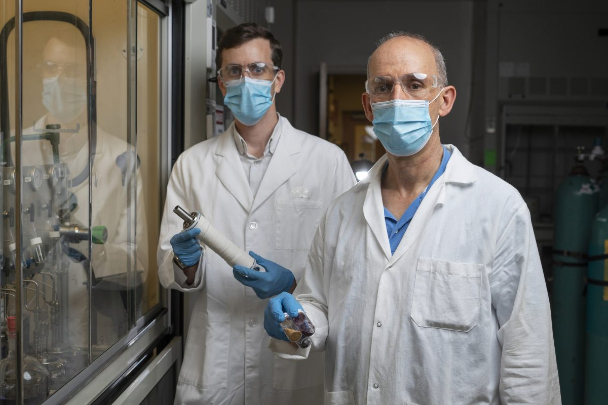 Georgia Tech Associate Professor Ryan Lively shows a module containing the new membrane material, while Professor M.G. Finn holds vials containing some of the other polymers used in this study.