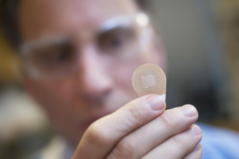 <p>Mark Prausnitz, Ph.D., Georgia Tech Regents professor in the School of Chemical and Biomolecular Engineering, holds a microneedle vaccine patch containing needles that dissolve into the skin. (Credit: Christopher Moore, Georgia Tech)</p>